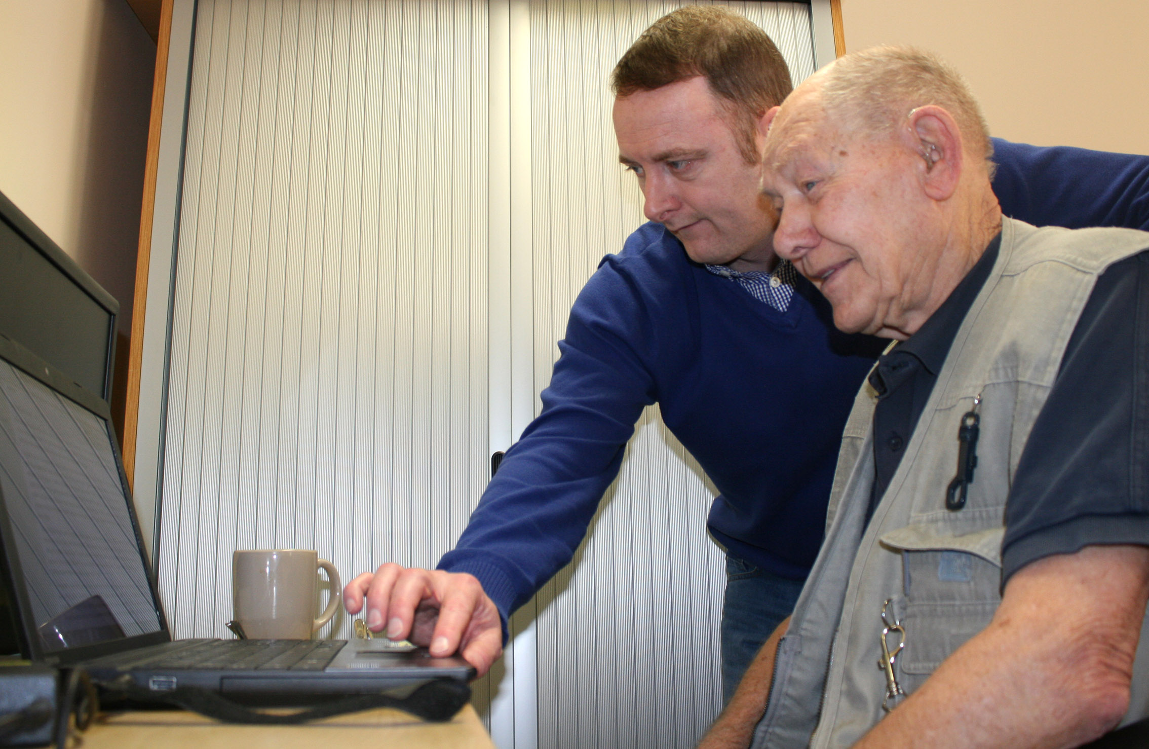 Mark Galvin (Age UK Oldham) teaching Doug Farrington on the laptop. Age UK Oldham computer classes