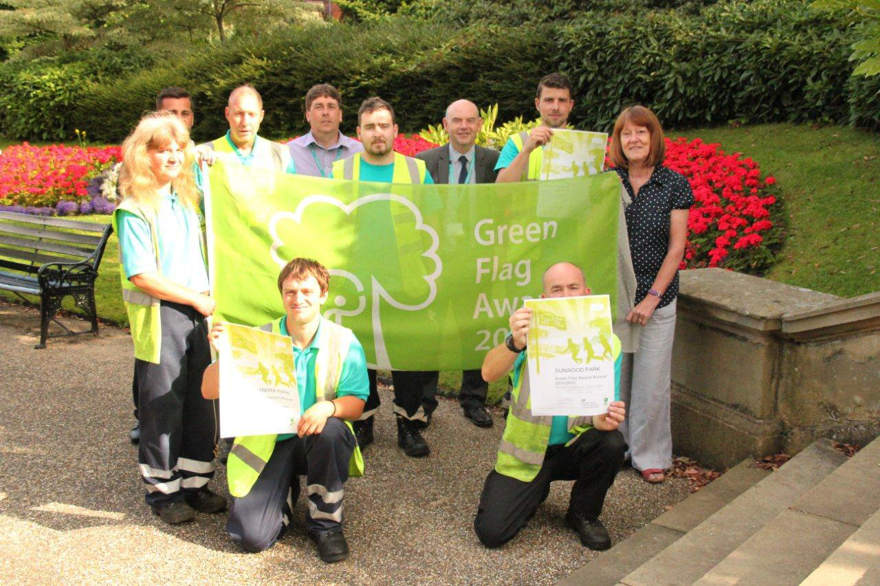 Councillor Barbara Brownridge, Cabinet Member for Neighbourhoods and Cooperatives (front right), with Oldham Council staff members and the Green Flag awarded to Alexandra Park.
