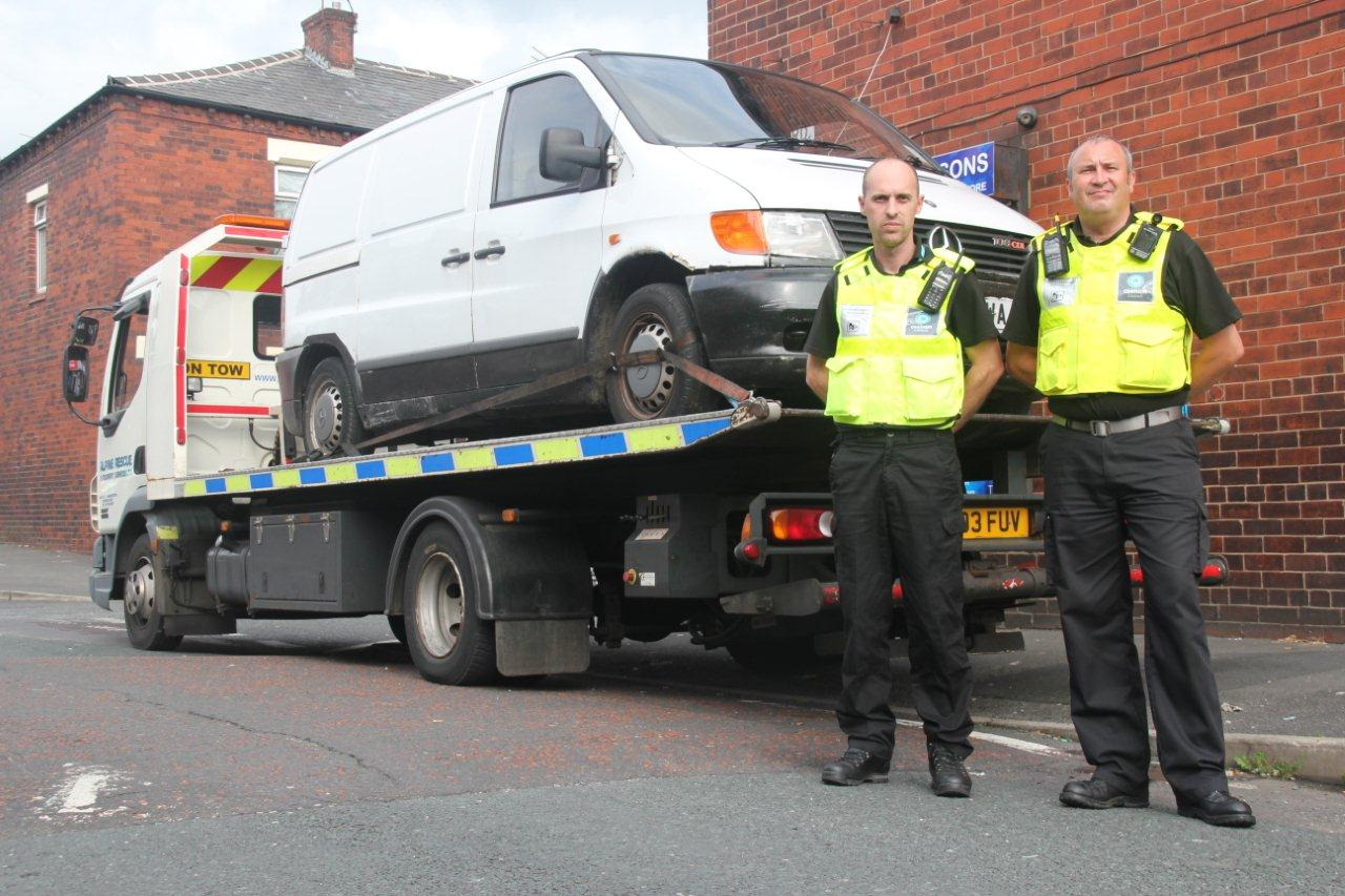 David Scanlon and Mark Greenhalgh, Oldham Council Neighbourhood Enforcement Officers, with the seized vehicle on Brewerton Road, Clarksfield, before it was impounded.
